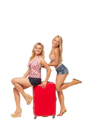 zwei schöne blonde Mädchen tragen Jeans-Shorts mit großen roten Koffer isoliert auf weiß