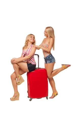 two beautiful blonde girls wearing jeans shorts with  big red suitcase isolated on white  Stock Photo