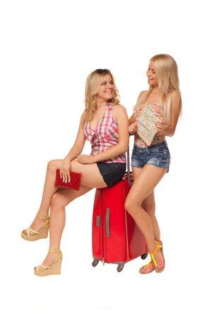 zwei schöne blonde Mädchen tragen Jeans-Shorts mit Karte und großen roten Koffer isoliert auf weiß Standard-Bild