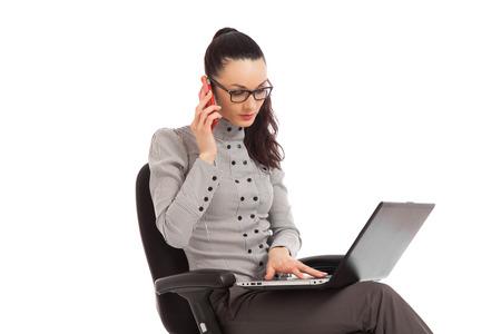 Unternehmerin sitzt im Bürostuhl mit Laptop im Gespräch am Telefon über weißem Hintergrund