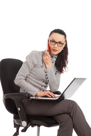 businesswoman sitting in the office chair with laptop talking on the phone over white background