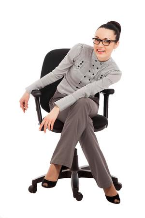 Brünette Frau in Hemd und Hose sitzt in Bürostuhl auf weißem Hintergrund Standard-Bild