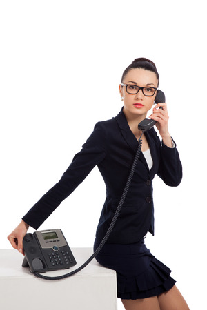 Brünette Frau trägt einen schwarzen Rock und Jacke Gespräch am Telefon und sitzen auf cube über weißem Hintergrund