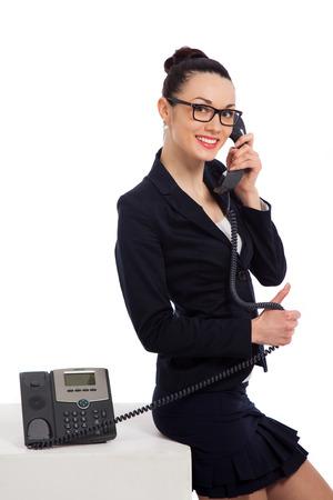 Brünette Frau tragen schwarze Rock und Jacke Gespräch am Telefon und sitzen auf cube über weißem Hintergrund