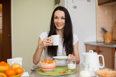 brunette girl driking tea in the morning in the kitchen with muesli and fruits