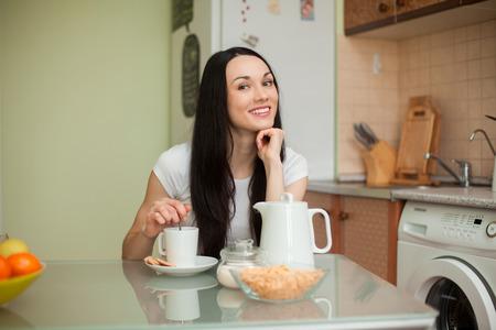 Brünette Mädchen trinken Tee mit Plätzchen in der Moring in der Küche Standard-Bild
