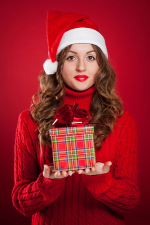 beautiful brunette girl in red sweater holding Christmas present wearing Santa Clause hat over red background