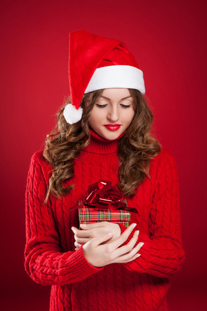 beautiful brunette girl in red sweater holding Christmas present wearing Santa Clause hat Stock Photo