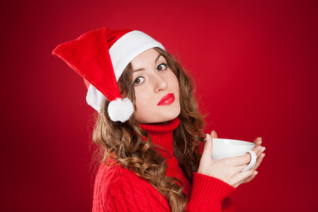 beautiful brunette girl in Santa Clause hat holding white mug  wearing red sweater  over red background