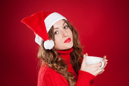 schöne Brünette Mädchen im Weihnachtsmann-Hut mit weißen Becher mit den roten Pullover über rotem Hintergrund