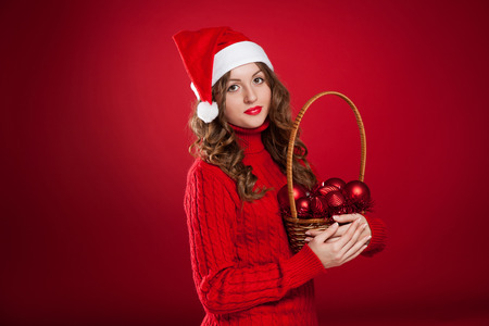 beautiful brunette girl with curly hair wearing Santa Claus hat holding basket with christmas tree decorations