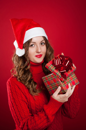 beautiful brunette girl in red sweater opening Christmas present wearing Santa Clause hat Stock Photo