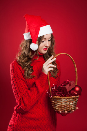 beautiful brunette girl with curly hair wearing Santa Claus hat holding basket with christmas tree decorations and little present Stock Photo