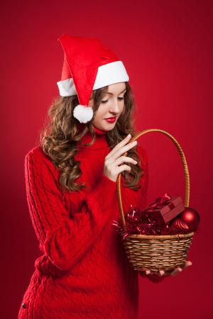 schöne Brünette Mädchen mit dem lockigen Haar trägt Nikolausmütze holding Korb mit Christbaumschmuck und kleines Geschenk