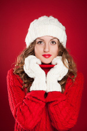 beautiful girl with curly hair wearing warm hat, mittens and red sweater over red background Stock Photo