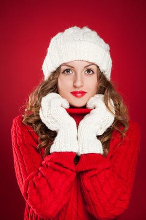 schöne Mädchen mit lockigen Haaren tragen warme Mütze, Handschuhe und roten Pullover auf rotem Hintergrund