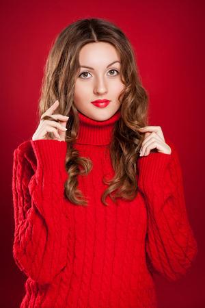 schöne Brünette Mädchen tragen rote Pullover über rotem Hintergrund