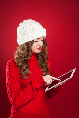 beautiful brunette girl wearing red sweater and holding touchs screen searing internet over red background