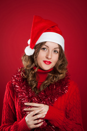 beautiful brunette girl wearing red sweater and Santa Clause hat holding garland over red background