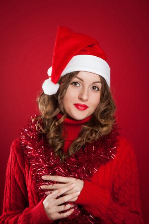 schöne Brünette Mädchen tragen rote Pullover und Weihnachtsmann-Hut holding Girlanden auf rotem Hintergrund Standard-Bild