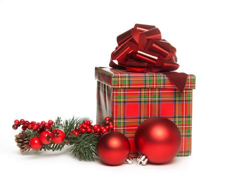 rotes Weihnachtsgeschenk mit Bogen, Mistelzweig und rote Kugeln auf weißem Hintergrund