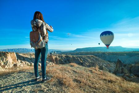 Female tourist taking photos of hot air balloon in Cappadocia Stock Photo