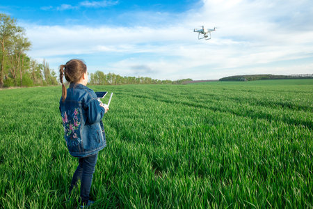 Little girl is operating the drone by remote control in the field