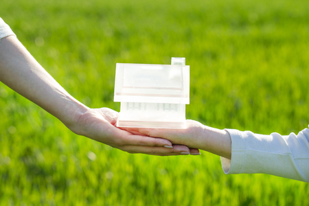 hands hold a house made for family concept in the green grass