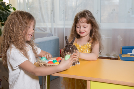 bunny girl: children play with a brown Easter Bunny. Next to them lay Easter eggs