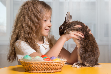 huevos de pascua: children play with a brown Easter Bunny. Next to them lay Easter eggs