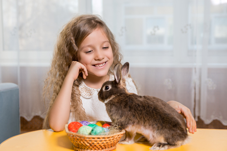 osterhase: children play with a brown Easter Bunny. Next to them lay Easter eggs