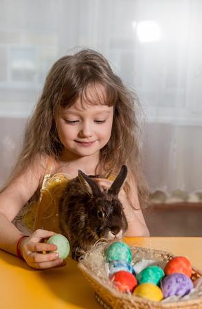 huevos de pascua: los ni�os juegan con un conejo de Pascua marr�n. Junto a ellos poner los huevos de Pascua