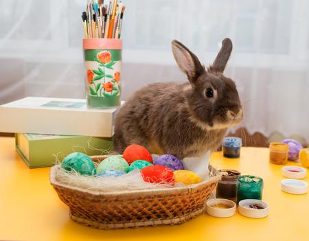 huevos de pascua: el Conejo de Pascua se sienta en una mesa. ni�as pintan los huevos