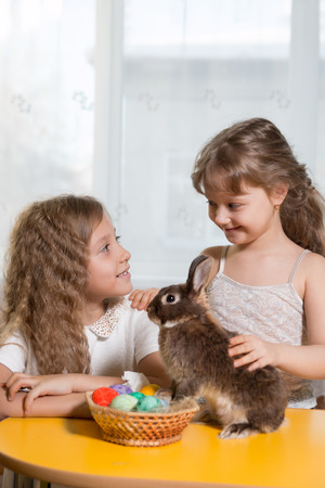 huevos pascua: two sisters  play with brown Easter Bunny. Next to them lay Easter eggs