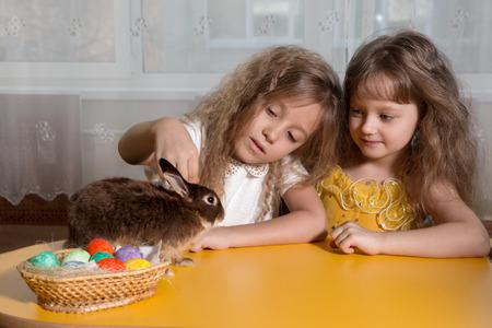 huevos de pascua: dos hermanas juegan con el conejo de Pascua marr�n. Junto a ellos poner los huevos de Pascua Foto de archivo