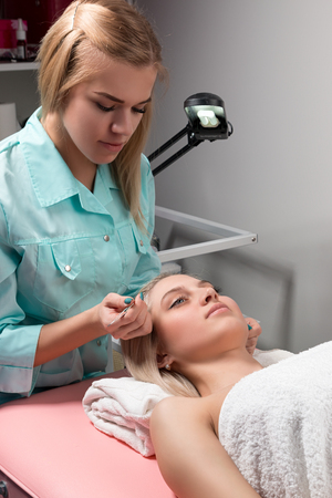 pluck: A cosmetician pluck eyebrows with tweezers  in a beauty salon. Cosmetician in a beauty salon behind work
