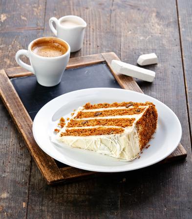 Slice of carrot cake on vintage slate chalk board background