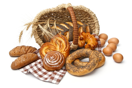 bread basket: Assortment of baked bread with wheat in basket isolated on white background
