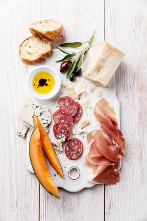 前菜のハム、チーズ、メロン、バルサミコとオリーブ オイル 写真素材
