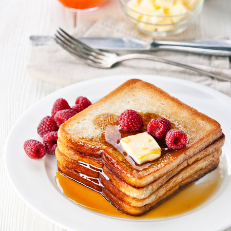 toast: French toast with raspberries, maple syrup and butter