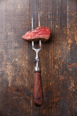 Piece of beef steak on meat fork on wooden background Banque d'images