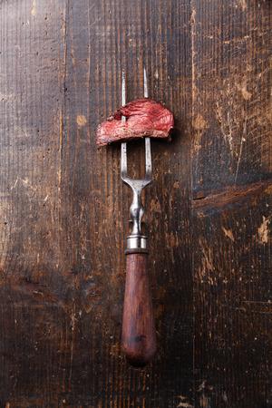 Piece of beef steak on meat fork on wooden background Archivio Fotografico