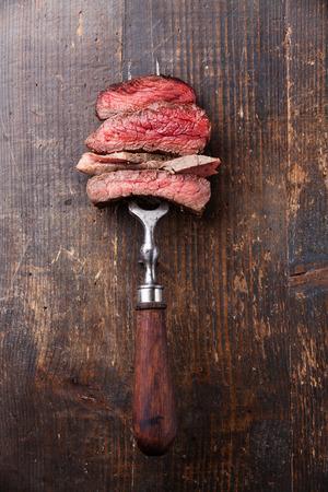 Slices of beef steak on meat fork on wooden background Banque d'images
