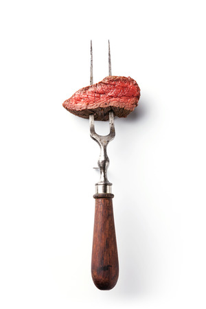 Piece of beef steak on meat fork on white background