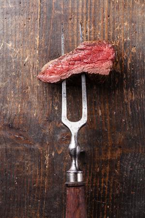 나무 배경에 고기 포크에 쇠고기 스테이크의 조각 스톡 콘텐츠 - 29006515