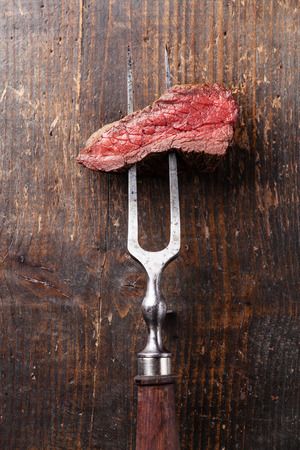 Piece of beef steak on meat fork on wooden background Imagens