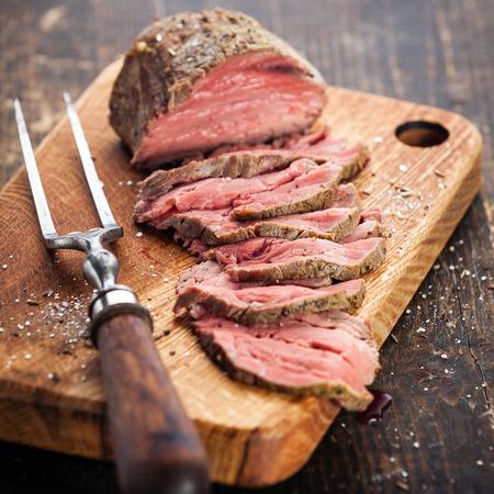 Arrosto di manzo su tagliere e forchetta carne Archivio Fotografico - 29006526