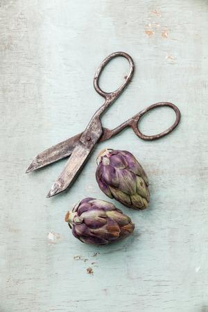 Two whole artichokes and vintage scissors on rustic wooden background Archivio Fotografico