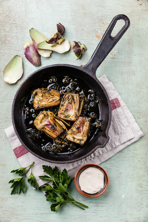 Pan with cooked artichokes on blue background Banco de Imagens