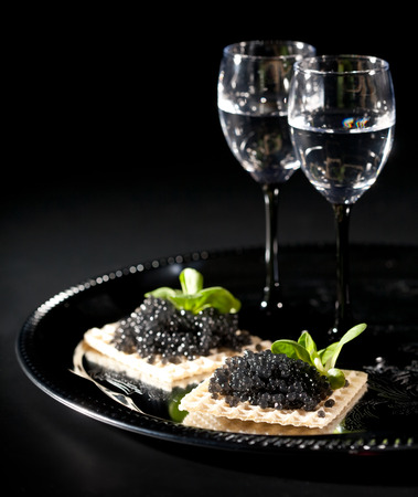 Vodka and black caviar on black background Banque d'images